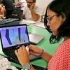 Estudante do curso de Design da UFC em laboratório trabalhando com computador e 3D